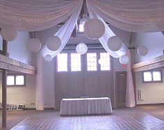 Classic white wedding - use large lanterns, draped material and fairy lights over the centre of the room to draw attention