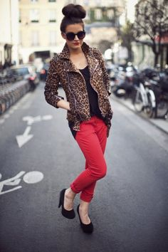 Motorcycle chic according to Frassy: a high bun, a studded leopard jacket, red jeans and black platform heels.