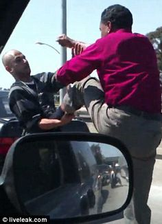 Fracas: Drivers can be heard honking their horns as the melee on the side of the road escalates