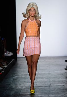 Gigi opened the Jeremy Scott show in a high-shine orange and pink coordinated set that was played up by a p...