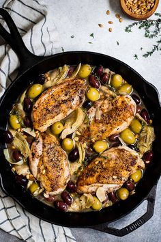 Extra juicy crispy-skinned garlic white wine skillet chicken with olives and artichokes served over a bed of pasta - an easy weeknight dish!