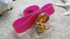 Ianthi Handmade ring made of fuchsia rubber, gold teddy bear and bead in honey colour.