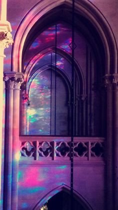 Colored fields of light reflect on the stone surface of the church as illuminations of the sun passing through the stained glass.