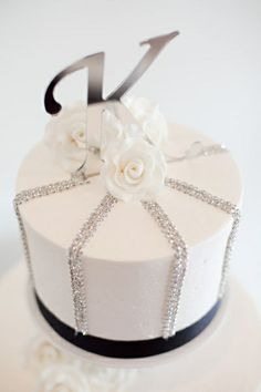 I love this small cake with the silver ribbon going vertically down the sides of the cake.  Perfect on a black stand and the white gumpaste flowers are just the right size.   ᘡղbᘠ