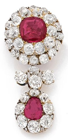 A 19th century antique Burmese ruby, diamond and 14K gold brooch/pendant, English. Set with a cushion-cut ruby, approx. 3 carats, framed by a double circle of old-cut diamonds, suspending a ruby pendant, approx. 2 carats, surrounded by diamonds. The pendant detachable. 4.4cm.
