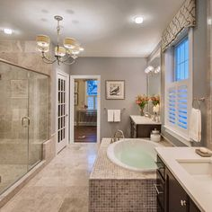 gray master bathroom with flush mount ceiling light and chandelier
