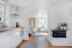 Modernt och ljus kök med vit skåpsinredning  och massiv oljad ekbänk. Bjurfors.se