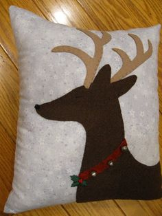 This simple yet lovely pillow features a pretty reindeer all ready for the Christmas season. Ive stitched the reindeer using tan and brown wool felt and added a red colored collar and silver bells to it. For the finishing touch Ive added a hand painted wooden holly leaves button. The