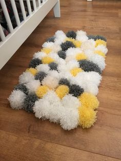 Gorgeous fluffy pom pom rug, perfect for a nursery to keep feet warm and cosy when soothing baby.  Made to order. Any mix of colours available on request. Colours shown are grey/white and yellow.  Soft wool, rubber mat grip on base.  Dimensions - approx 55cm x 45cm  *Not machine washable, recommend you clean with a damp cloth*