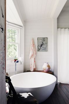 Round grey bathtub, white walls, wooden floors, and white shower curtain