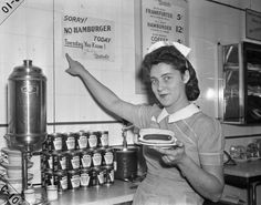 "A waitress in a Nedick's restaurant in New York, pointing to a sign indicating the wartime ""Meatless Tuesday,"" practice which was encouraged in NYC in 1942. #truenewyork #lovenyc"