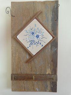 Em madeira de demolição com azulejo. Peça única contendo três ganchos para pendurar chaves.