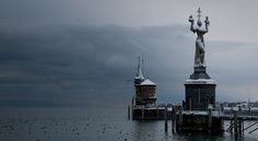 https://flic.kr/p/93xYnK | Konstanz, Germany (Bodensee) | A view of the snow-laden clouds over the Bodensee, near the harbor entrance. Civilization in Konstanz traces to the late Stone Age, and was first settled by the Romans around 50 AD. Konstanz has an amazing history for such a small town. The statute to the right is the Imperia, a satirical commemoration of the Council of Konstanz (1414-1418) during which the only election for a Pope ever held North of the Alps took place.