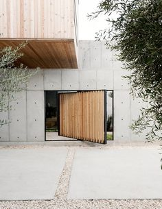 This Texas home incorporates Japanese influences with cubes of different materials. There are three main boxes, two concrete forms and a lifted wooden cube. Click through for more images of this minimalist home. This big pivoting door leads from a zen garden into the home.