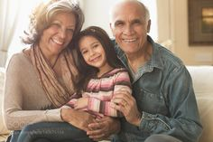 Grandparents and granddaughter smiling on sofa by gabledenims