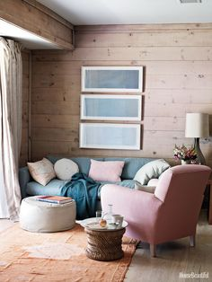 """Interior designers Maxwell Macdonald and Andrew Corrie gave this Shelter Island, New York, beach house a relaxed vibe. The pink-and-blue living room's washed wood walls give it a beachy feel. """"We kept all the fabrics to natural, muted tones, and it's all of the colors you see in the views — whites, grays, blues, a bit of pale pink,"""" Macdonald says. Ditte Isager - HouseBeautiful.com"""
