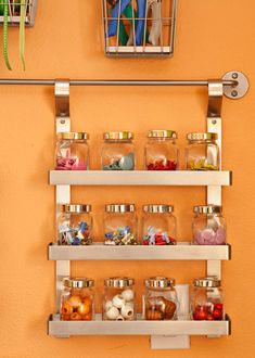 For visible storage, line up jars housing small embellishments and notions in a spice rack.