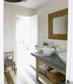 """""""This bathroom console in the guesthouse was an antiques fair find,"""" says designer Ginger Barber. """"It's all about the back and forth, crisp white vessel sinks and white walls against the worn zinc top and rustic baskets.""""   - HouseBeautiful.com"""
