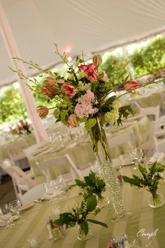 table decor - feathers in the tall glasses and flowers in the small ones