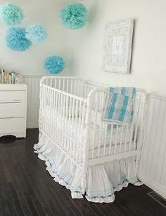 inthefunlane.com  Adorable nursery design with light gray walls, white vintage crib, beadboard, blue  green paper pom poms, baroque frame and espresso wood floors.