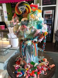 Here's what's in it: blue or pink cotton candy ice cream layered with cotton candy, sweet and sour candies, ice cream cone, whipped cream and marshmallow sauce. It is then finished with some sprinkles and a whirly pop. You'll definitely want to bring somebody to share with!