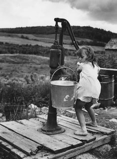 +~+~ Vintage Photograph ~+~+ Young girl gathering water from the pump well. Aroostook County, Maine, 1942 (looks like this lil' girl was quite used to pumping water. Vintage Pictures, Old Pictures, Old Photos, Photo Vintage, Vintage Farm, Vintage Country, Black White Photos, Black And White Photography, Old Water Pumps