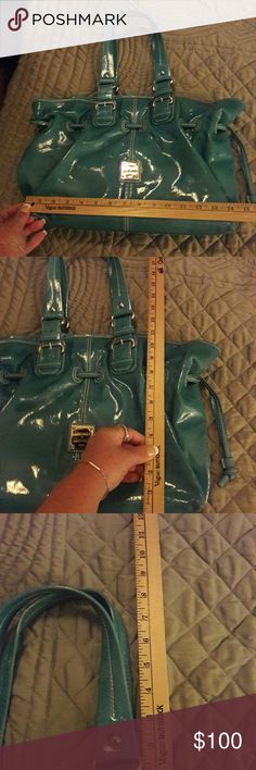 Vintage Dooney Bourke Aunthenthic, EUC vintage Dooney Bourke patent leather bag. Large, color teal. Color is Accurate as described in pictures. This bag is in Pristine condition with the exception of the very small flaw shown in picture #5. It's a pink color cloth inside no stains tears or odors, with a middle divider a zip pocket. I very small . I've never seen another bag like this one. Gorgeous! Part of my collection I have too many D&B's purses in general.  Would like to find it a new…