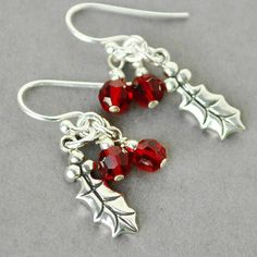 Sterling silver holly earrings with red swarovski crystal berries. The swarovski crystal earrings measure 1 1/4 long and are on sterling silver ear wires. Perfect christmas earrings. ALL STERLING SILVER * 6mm siam swarovski crystals * sterling silver holly leaf (16mm) *