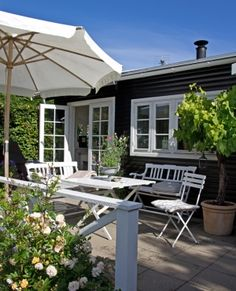 Relaxing summer house patio with simple white wood furniture.