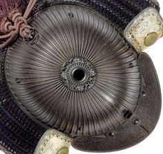 Sixty-two-ken koseizan shaped suji bachi kabuto, by Fujiwara Iehisa, early Edo Period, 17th c, the edges of the suji are folded over to double the thickness, bowl interior lacquered gold, hon kozane komanju jikoro, six-stage tehen kanamono, kosho-no-kan, hasso kanamono and the roped fukurin on the fukigaeshi all in shakudo, Fujiwara Iehisa was a member of the Haruta group of armourers, his work is rated Jo Jo I (excellent).