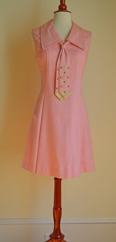 This 1960's MOD Scooter Shift Dress is the sweetest light pink color juxtaposed with a large pointed collar and attached tie embellished with gold studs and tips all on a silhouette that goes with her curves and flares out at the hem. The collar and tie mean business but the bubblegum color is not to be taken seriously and the scooter shape is for the girl who knows how to have fun, a collaboration of elements to suit all your complexities.