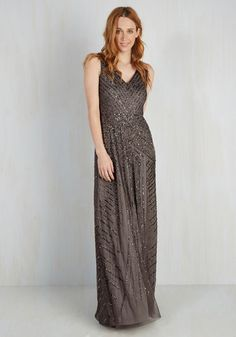 Your elegance is well-articulated with this glimmering Adrianna Papell gown! Beneath the chevron-detailed bodice of this floor-length dress lies deco-inspired patterns, shimmering with deep silver beading and sequins, and giving this charcoal grey frock an unparalleled air of refinement.
