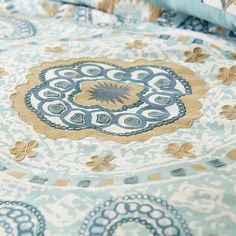 """Spanish for """"coast,"""" our Costa bedding promotes a leisurely vibe with its subdued aqua and neutral tones, large embroidered medallion and sumptuous 100% cotton construction. Generously sized, the duvet covers feature inside ties at the corners to keep your insert from shifting. And you'll relax even more knowing that it's machine-washable."""