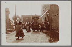 Scharensliep op de dijk. 1900-1906 Scharensliep op de Haven tussen Ghislein Tol rechts en Hotel Spaander links. Het meisje in dracht op de voorgrond gaat een boodschap doen. Ze draagt een fles waarmee ze bij Thaampie van Koppie een half maatje sterke drank gaat halen. #NoordHolland #Volendam