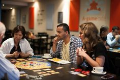 Left to right: Jane Swaine, Geraldo Neto and Corinna Howard join others in playing a special edition game of Catan at A-Game Cafe.
