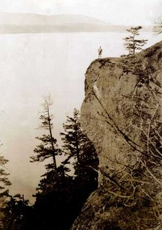 Faded postcard with photo of a lone man standing on Mt Galiano on Galiano Island looking NW.