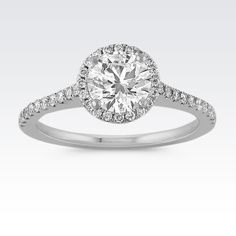 Dazzling and delicate, this gorgeous engagement ring features one round diamond, at approximately 1.00 carat, immersed within a lovely halo setting while a platform of diamonds sit beneath. The center round diamond is approximately I1 in clarity and F to I in color.  Fifty-nine round diamonds, at approximately .31 carat TW, are crafted in quality 14 karat white gold. The total diamond weight is approximately 1.31 carats.