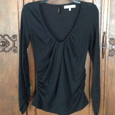 "MM Couture Ruched Top This jet black long sleeve T has a deep scoop neck with a twisted ruched center. Elasticized ruching at both sides of the waist and a wide waistband. There are elasticized gathers at the interests as well. Keyhole button clothes at the back of the neck. This top is pre-loved by me but is in good condition. ☺️16"" across at bust. 26"" length. MM Couture by Miss Me Miss Me Tops"