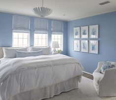 White and blue cottage bedroom boasts walls painted cornflower blue fitted with windows dressed in blue chevron roman shades placed over a white slipcovered headboard on king bed dressed in soft white bedding and a blue chevron lumbar pillow illuminated by a white pendant, Aerin Hampton Pendant, placed next to a wall lined with a blue coral art gallery.