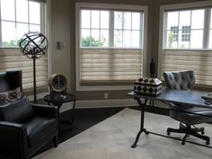 The soft linen textured folds of top/down bottom/up Vignette® Modern Roman Shades infuse a relaxed and comfortable vibe in this home office with industrial chic styled decor. ♦ Hunter Douglas window treatments