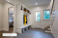 Informal entryway features white glass pane front door leading to foyer with built-in mud room ...