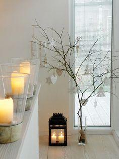 Dekoidee zu Weihnachten mit Kerzen, laterne und baum mit weißen Anhängern.