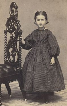 Child dressed in black with bobbed hair cut due to mourning. Her hair was likely used to create mourning jewelry.