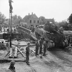 A Sherman tank and infantry of 11th Armoured Division cross a canal at Someren in The Netherlands, 24 September 1944.