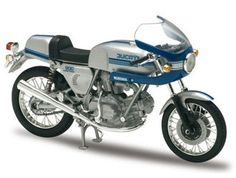 This Ducati 900 SS (1977) Diecast Model Motorcycle is Silver and Blue and features working stand, steering, wheels. It is made by Solido and is 1:18 scale (approx. 11cm / 4.3in long).  ...