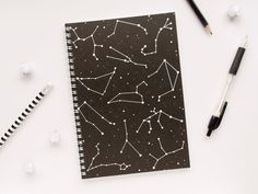 This notebook features the star sign constellations on a black background with speckled stars across the whole cover.