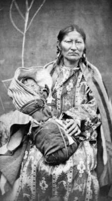 Studio portrait (sitting) of Spotted Tail's wife and baby, Native American (Brulé Sioux) woman and child. She wears a dress and blanket shawl. The baby is wrapped in swaddling clothes and blankets. Date[between 1875 and 1885]