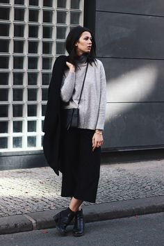 Elisa from the Fashion- and Lifestyleblog www.schwarzersamt.com is wearing a minimalistic autumn winter look with black culotte from Topshop, a Topshop sweater in light grey, a black coat from H&M and black high chelsea boots. The whole look is monochrome in black and grey.