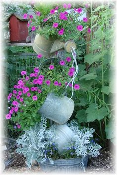 Pretty version someone came up with for tipsy galvanized buckets filled with wave petunias, dusty millers & lobelia and being watered down with clear wired beads pouring from watering can.