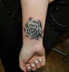Bonita rosa blanca tatuada en la muñeca